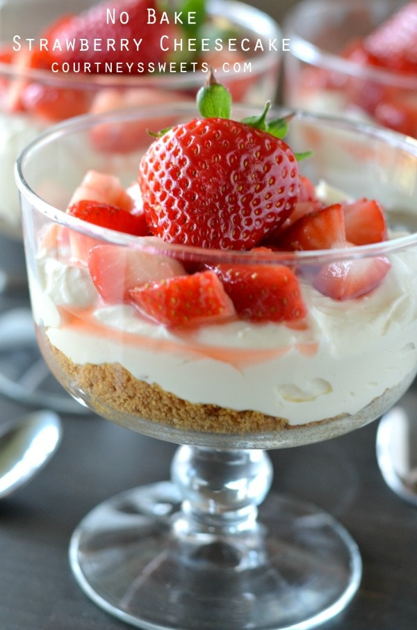 A glass bowl of cream with strawberries