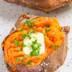 Our Air Fryer Baked Sweet Potato recipe results in a sweet potato baked to perfection! - Topped with butter, salt and parsley.