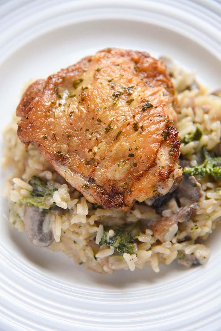 crispy chicken thighs over mushroom broccoli with rice