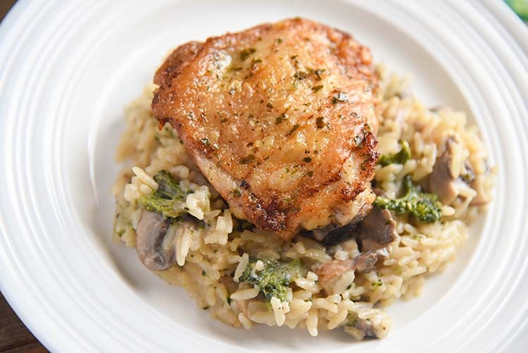 crispy chicken thighs over mushroom broccoli rice on a plate