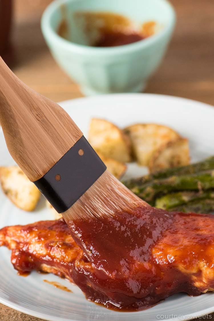 homemade bbq sauce on bbq brush basting chicken breast