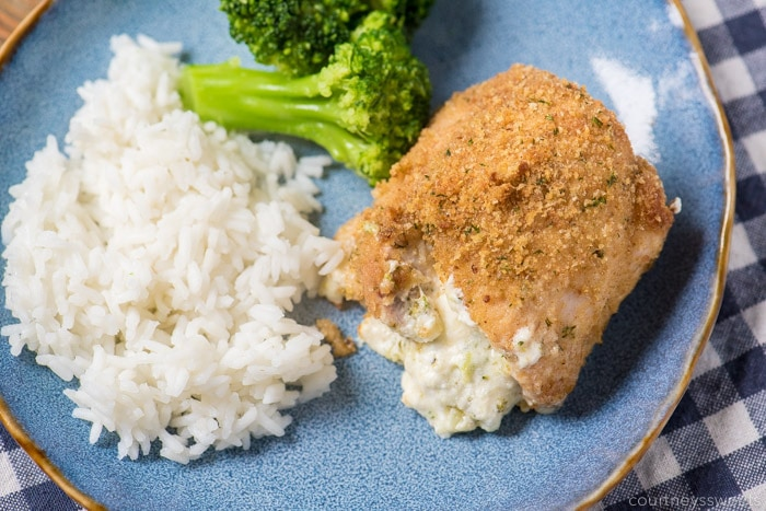 broccoli and cheese stuffed chicken thighs on a blue plate with rice and broccoli
