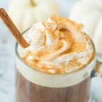 pumpkin spice coffee with whipped cream dusted with cinnamon and cinnamon stick