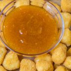 sweet and sour sauce in a bowl with mini chicken nuggets