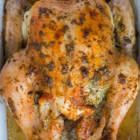 whole roasted chicken with herbs in a casserole dish