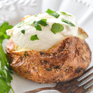 seasoned air fryer baked potato with sour cream and parsley garnish