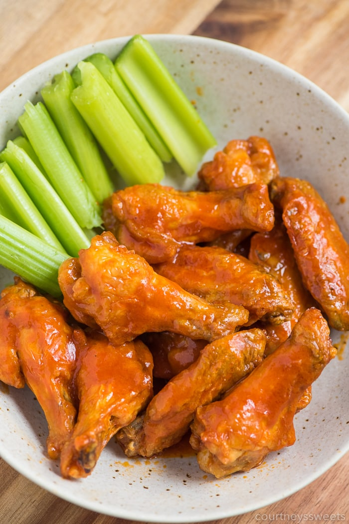 Air Fryer Chicken wings with hot sauce and celery in a bowl