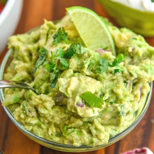 fresh guacamole in a bowl with lime garnish