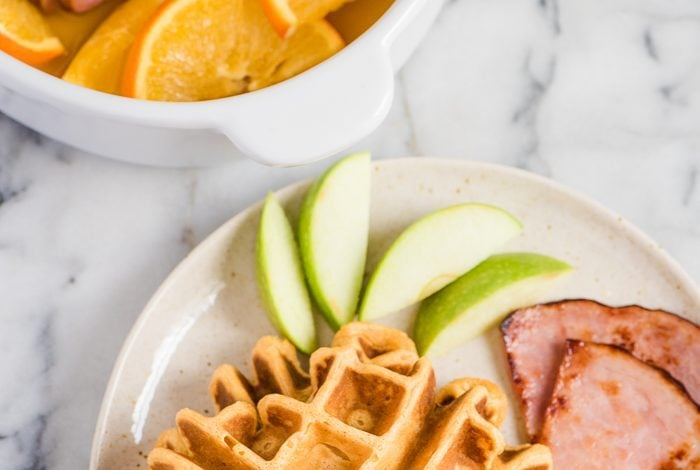sweet potato waffles with ham steaks on a plate with sliced apples