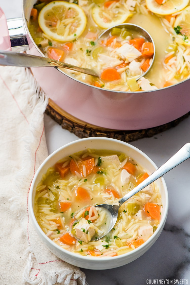 lemon chicken orzo soup in a ladle with pot
