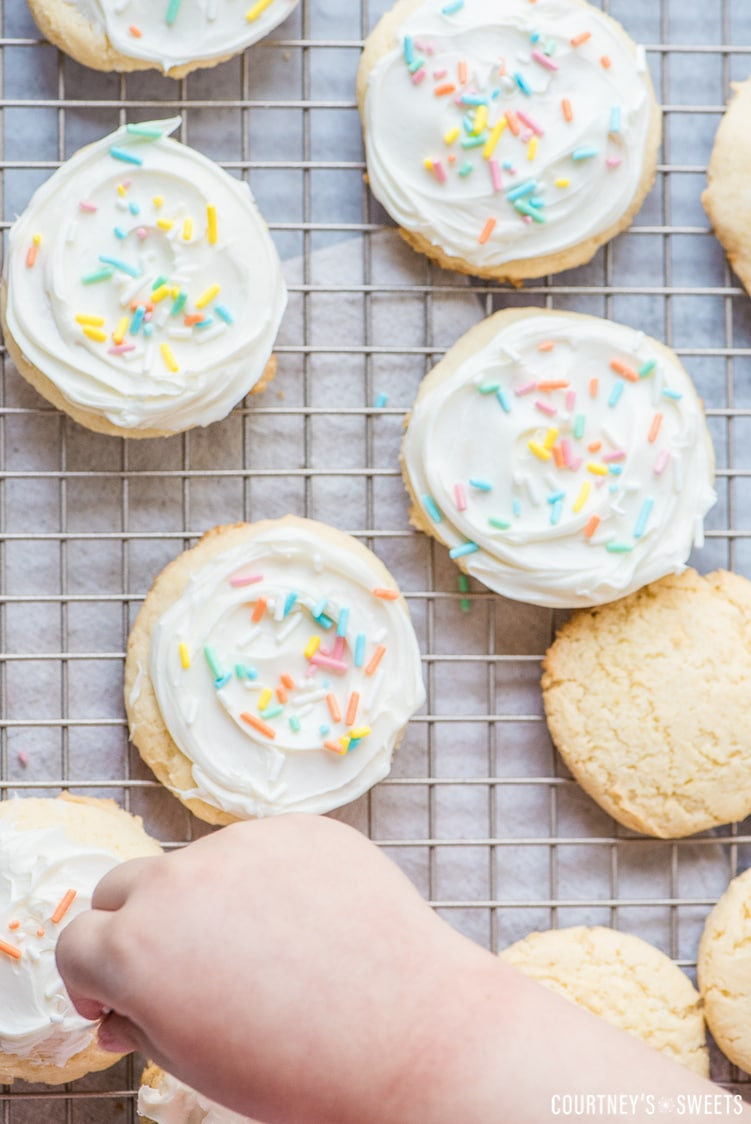 hand sprinkling rainbow sprinkles on white cake mix cookies