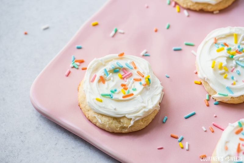 close up white cake mix cookies with vanilla frosting and rainbow sprinkles