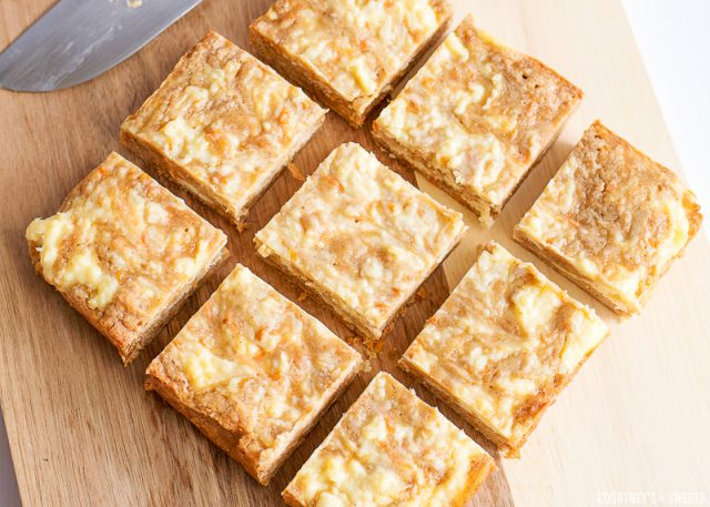 cut carrot cake bars on a cutting board