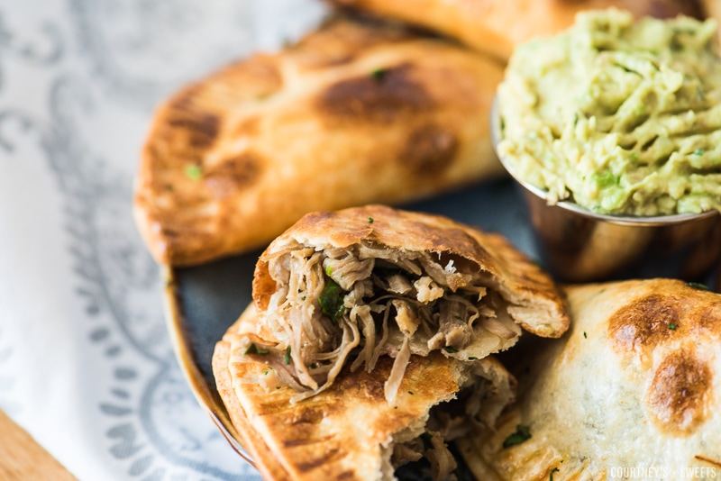 cut open pork carnitas empanadas on a plate
