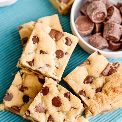 overhead photo of chocolate chip cookie bars with rolo candies in a bowl on a teal napkin