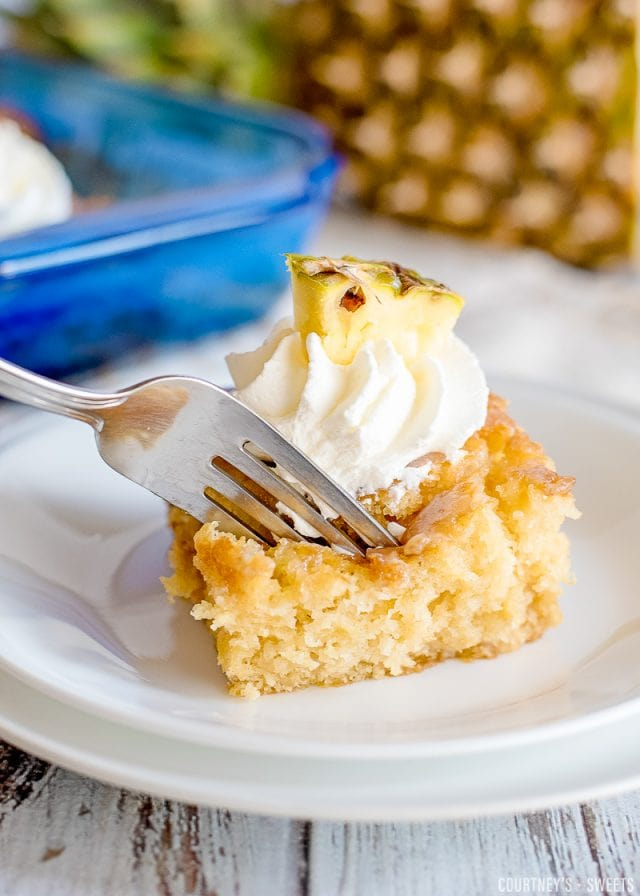 pineapple poke cake slice on a plate with fork