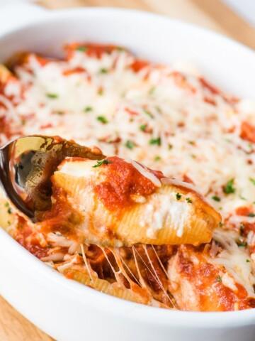 ricotta stuffed shell on a spoon in a casserole dish