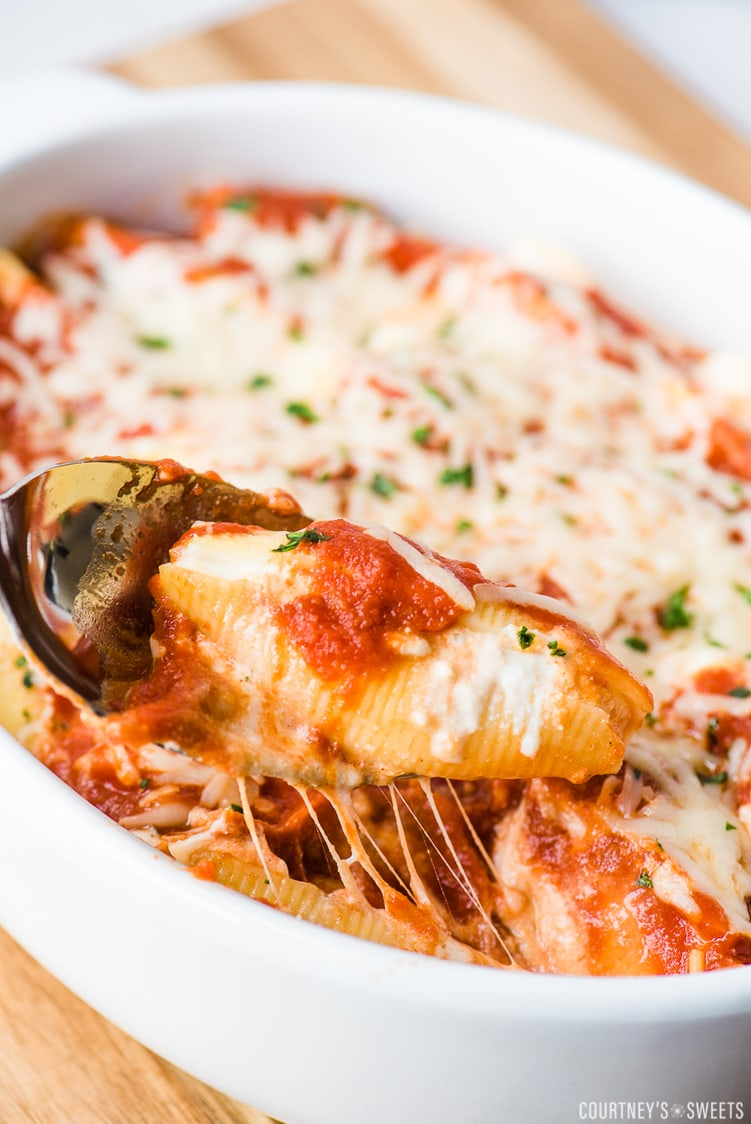 ricotta stuffed shell on a spoon in a casserole dish