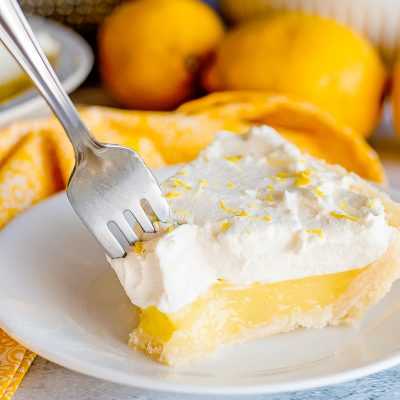 lemon pie with a fork in it on a plate with fresh lemons in background