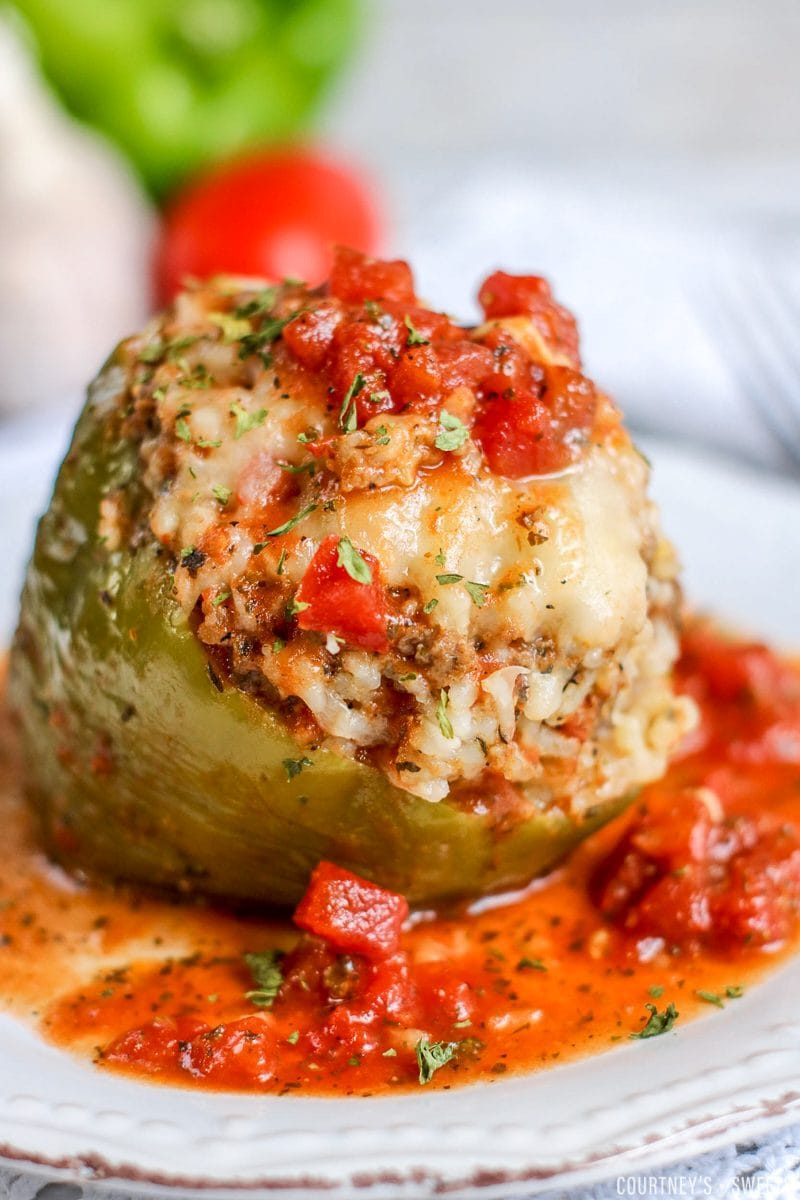 instant pot stuffed pepper on a plate covered in chunky tomato sauce