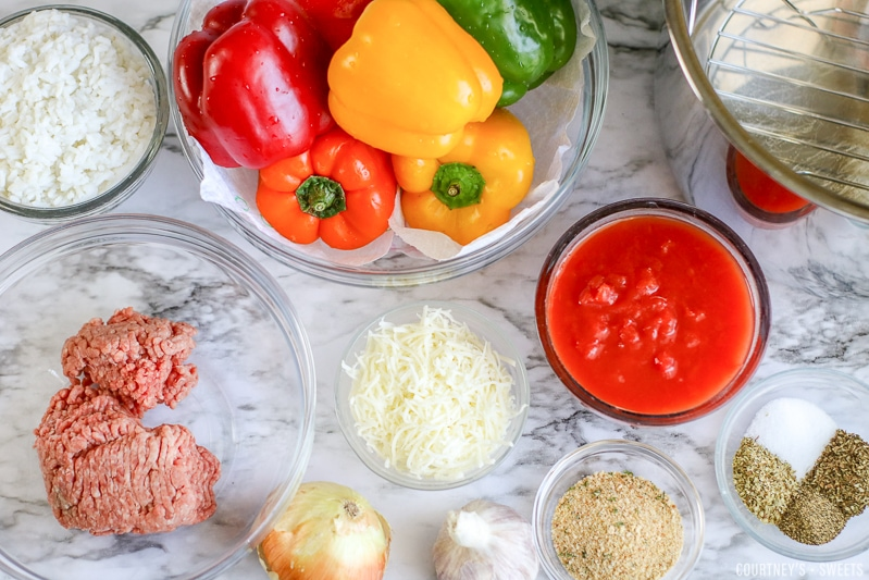 bell peppers in a bowl with ingredients to stuff