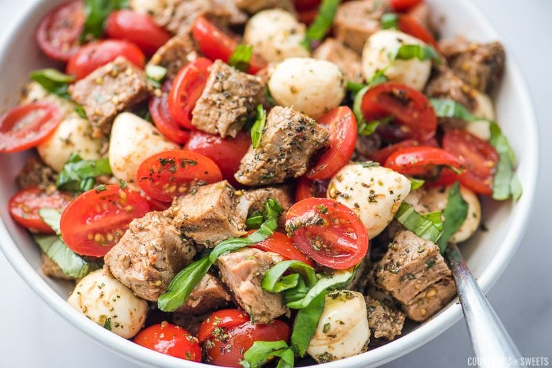 caprese salad with pork loin in a bowl with spoon, garnished with chiffonade of basil