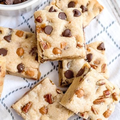 salted caramel chocolate chip cookies bars with pecans on a napkin