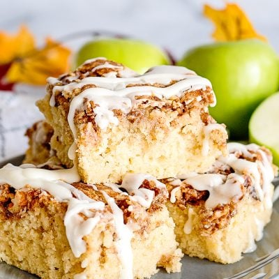 apple fritter breakfast cake sliced and stacked on a gray plate with granny smith apples in background