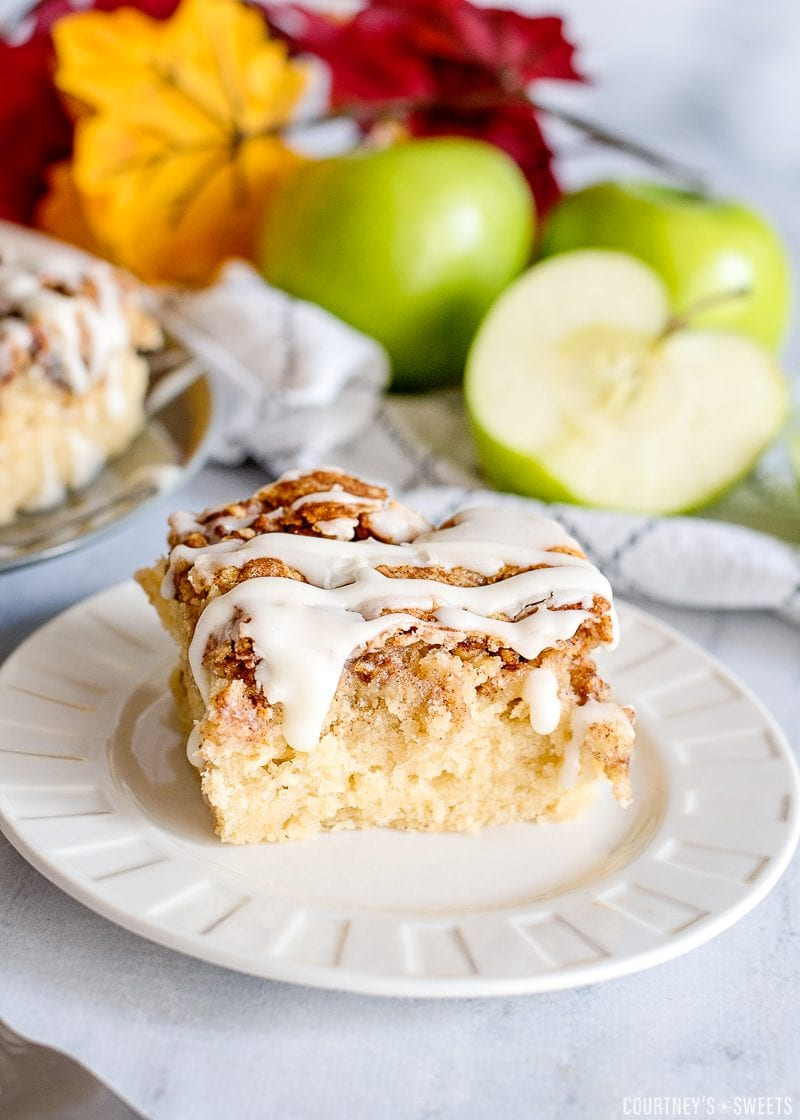 apple cake on a white plate with granny smith apples and leaves in background