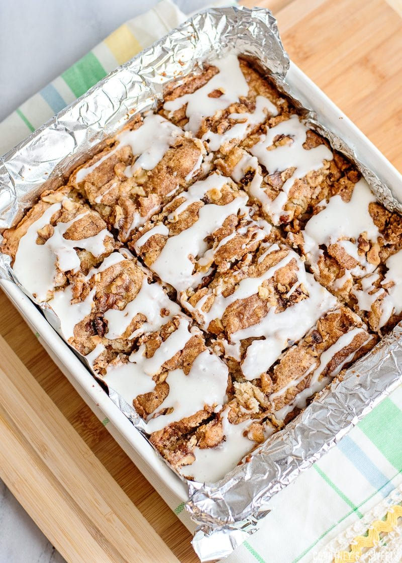 sliced apple cake in a baking pan with glaze