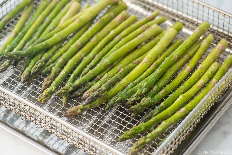 uncooked seasoned asparagus in air fryer basket