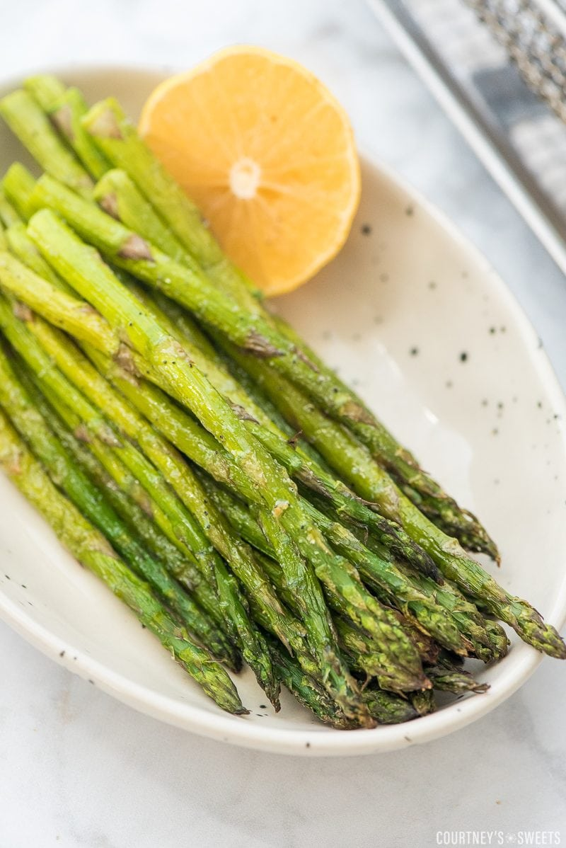 air fried asparagus in a bowl with a lemon wedge