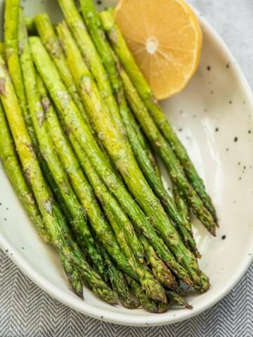 roasted asparagus in a bowl with half a lemon