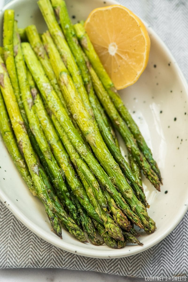 roasted asparagus in a bowl with half a lemon