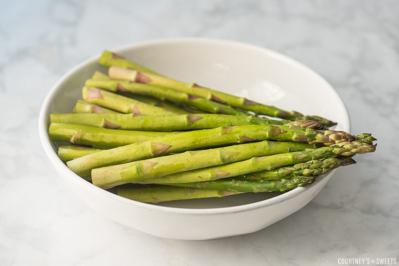 raw asparagus in a white bowl