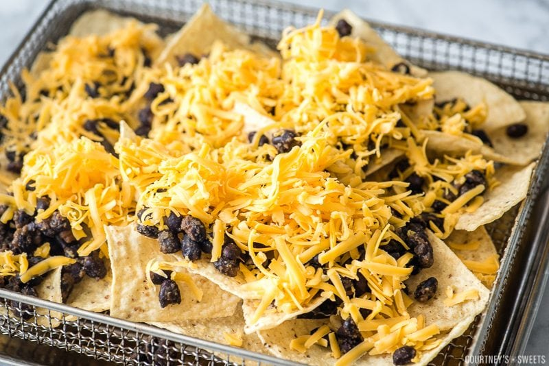tortilla chips with black beans and shredded cheddar cheese in cuisinart air fryer rack