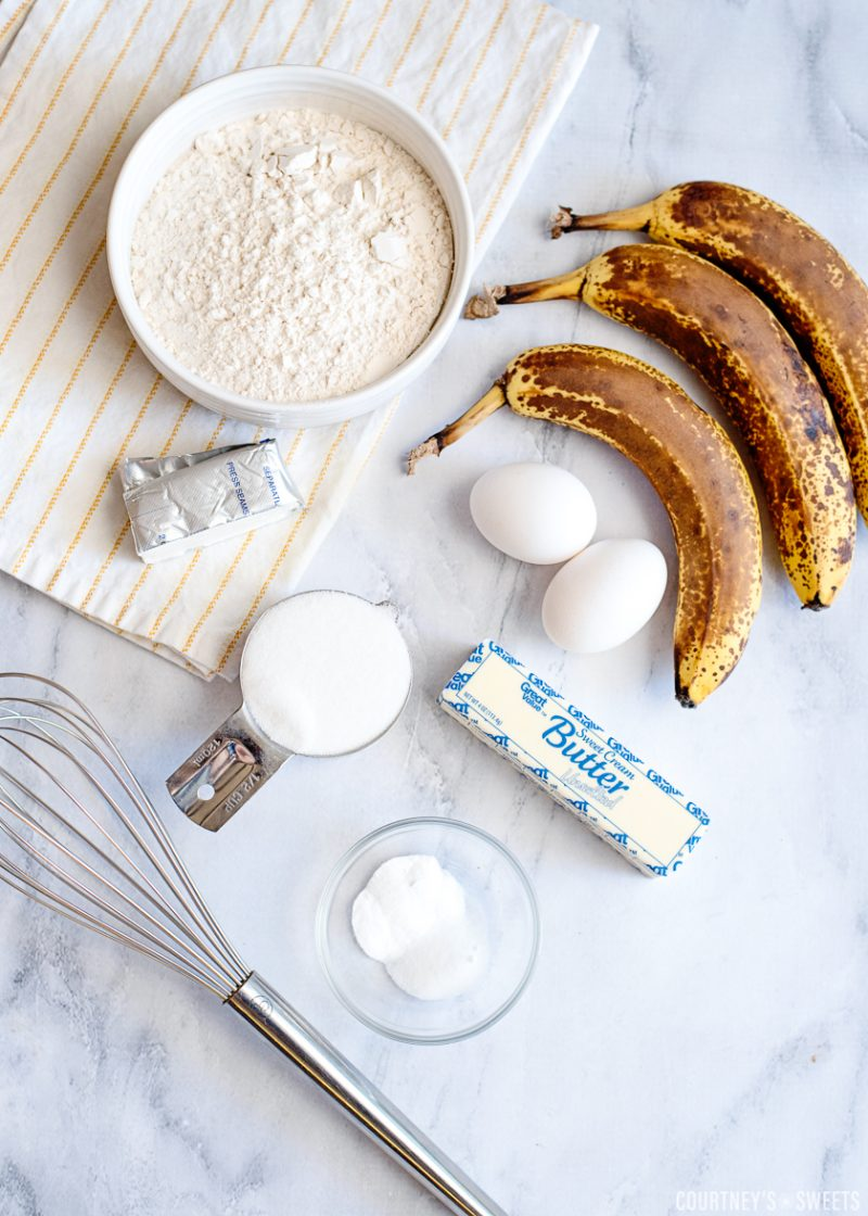 bananas eggs butter stick sugar flour in bowls and a metal whisk on a marble table top with striped white and yellow linen