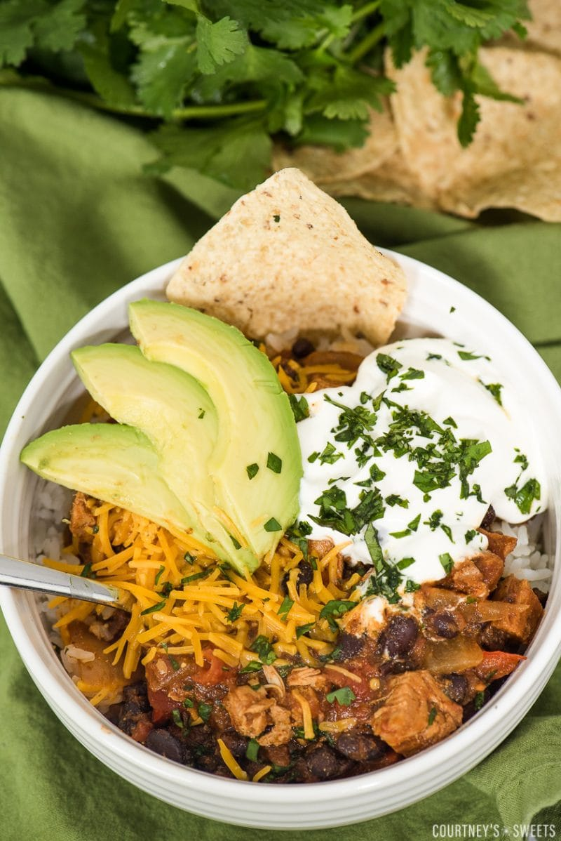 chili in a bowl with cheddar cheese sliced avocado sour cream and chopped cilantro