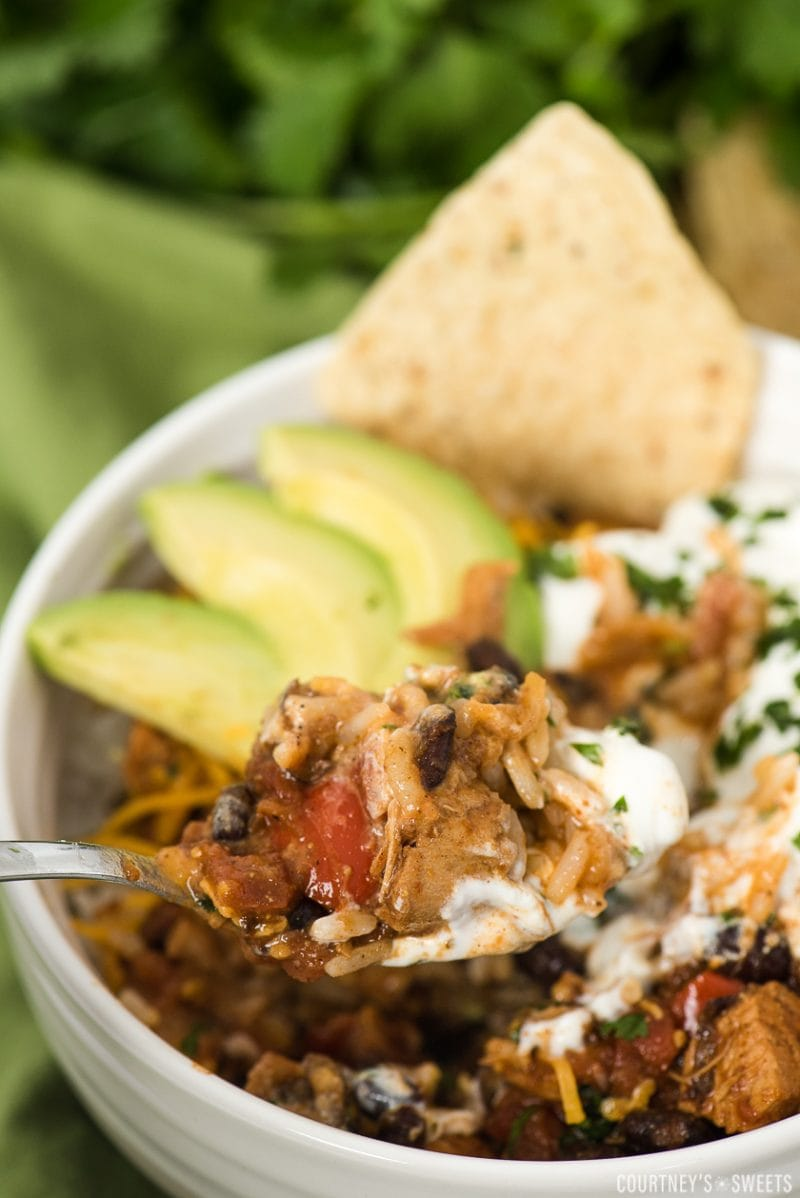 black bean chicken chili in a bowl over rice with loaded toppings on a spoon
