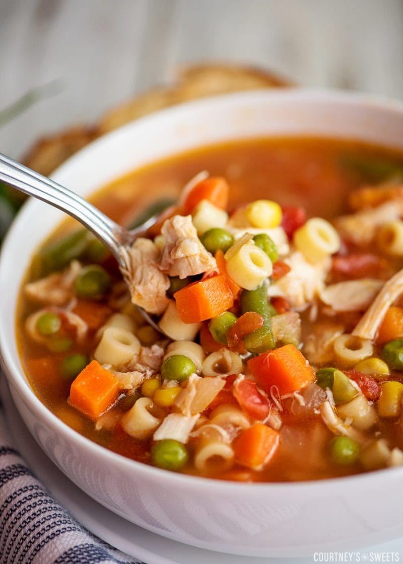 close up shot of chicken vegetable soup on a spoon in a white bowl