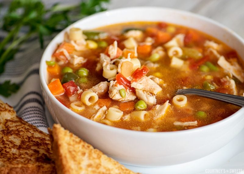 chicken vegetable soup in a bowl with a spoon and bread on plate