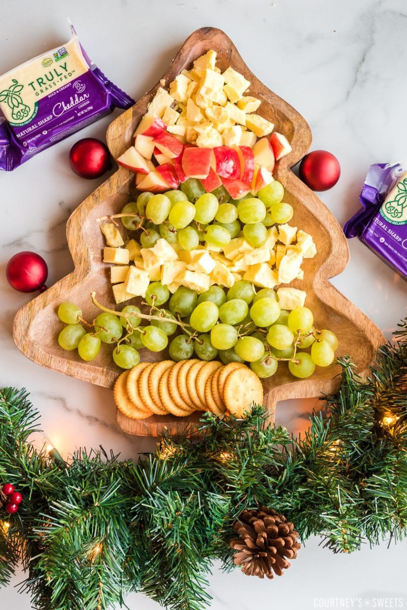 christmas tree cheese platter with fruit, cheese, and crackers chopped on a christmas tree shaped board with garland on the bottom for decoration and a block of truly grasfed cheese on either side
