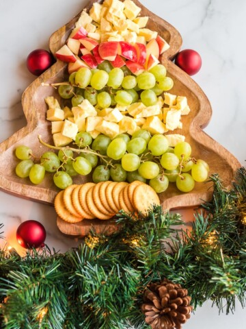 christmas tree cheese platter with fruit, cheese, and crackers chopped on a christmas tree shaped board with garland on the bottom for decoration
