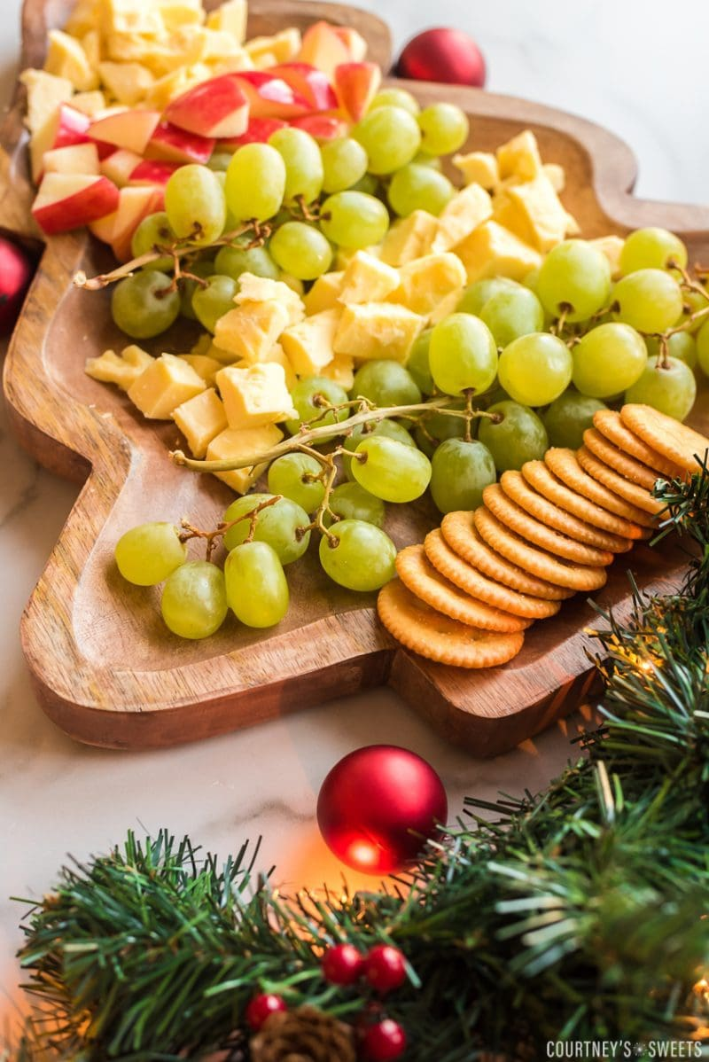 christmas tree shaped board with fruit and cheese on it with crackers and garland decor on the bottom