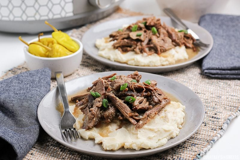 mississippi pot roast on two gray plates over mashed potatoes with peppers in a white bowl and gray napkins next to plates