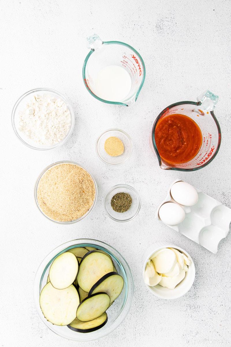 eggplant parmesan ingredients in bowls on a marble slab