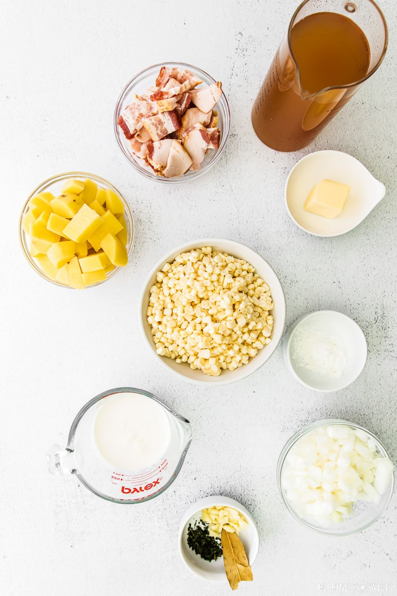 potato corn chowder ingredients in various bowls on a marble slab