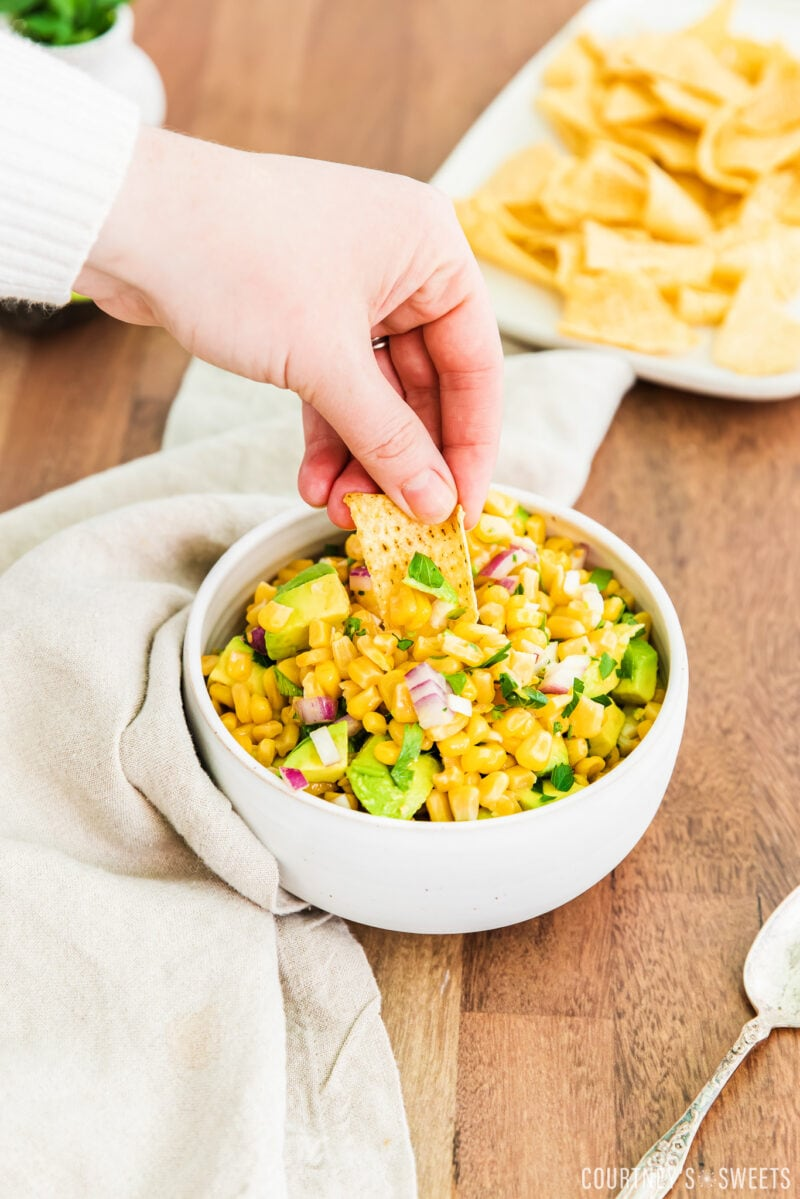 hand dipping chip into avocado corn salsa in a white bowl with linen napkin to the left