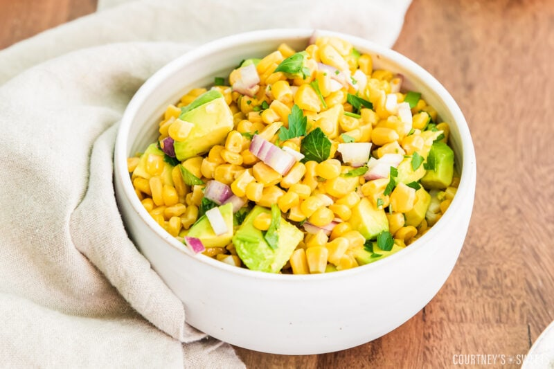 close up of avocado corn salsa in a white bowl with linen napkin to the left