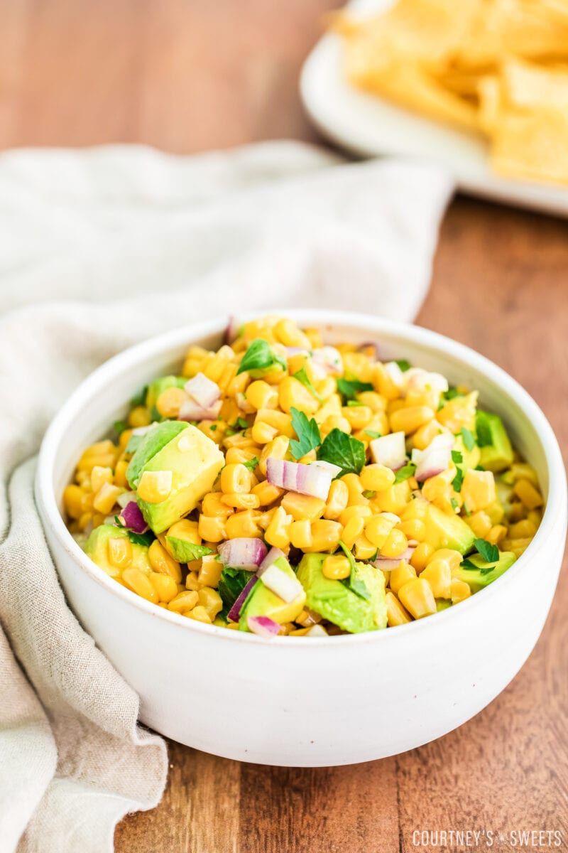 avocado corn salsa in a white bowl with linen napkin to the left